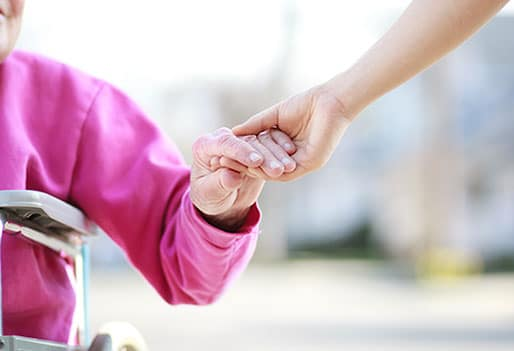 elderly person in a wheelchair holding hands with speech therapist